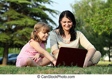 girl and child with laptop in park