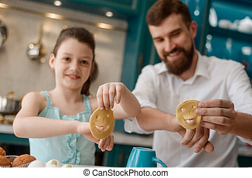 Girl and dad play with dough in kitchen, while making cookies