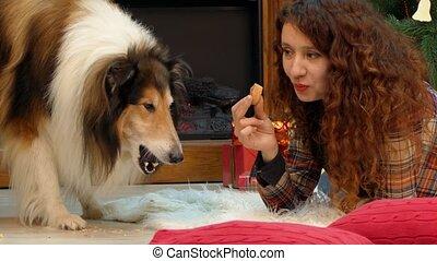 Girl and dog eating cookies at the Christmas tree - Girl and...