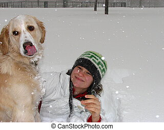 Girl and dog in snow - A girl sitting with her dog in the...