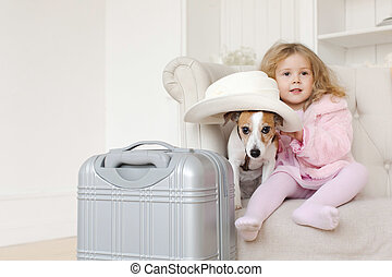 Girl and dog sitting near suit case