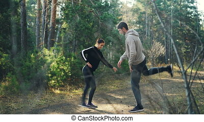 Girl and guy are doing sports in forest together moving legs...