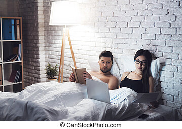 Girl and guy are in bed. The guy reads the book before going to bed. Girl working on laptop in bed.