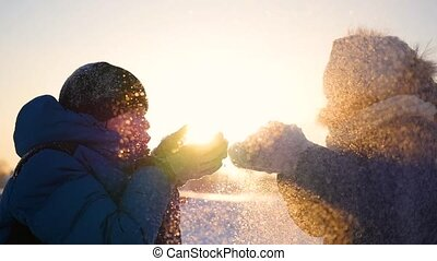 girl and guy blows snow with hands on sunset background. snow winter landscape. Sunset time