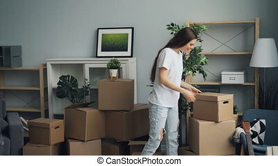 Young attractive girl and guy are carrying things in carton boxes during relocation in new apartment talking and smiling. People, house and lifestyle concept.
