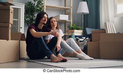 Girl and guy couple speaking sitting on floor in new apartment with carton boxes