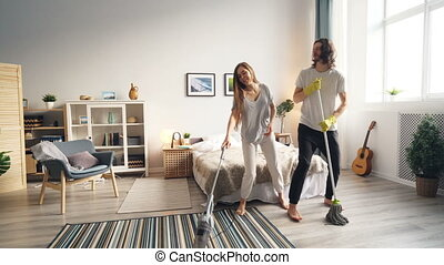 Girl and guy doing housework and having fun with vacuum cleaner and mop singing