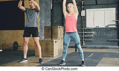 Girl and guy in sports outfit are squatting with kettlebells during crossfit training in gym, people are focused on bodybuilding power exercise. Youth and sports concept.