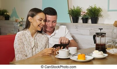 girl and guy looks at mobile phone at table in sweet shop