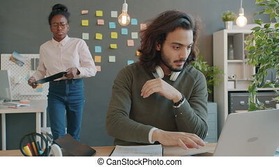 Girl and guy multi-racial team are working in office talking looking at paperwork at desk, woman is approaching man with charts and graphs in folder.