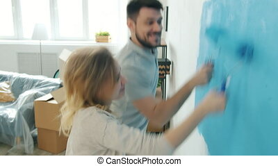 Girl and guy painting wall in studio dancing and laughing having fun during remodelling house