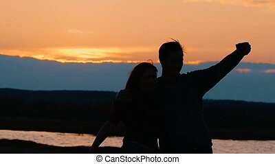 girl and guy photographed silhouette slow motion video -...