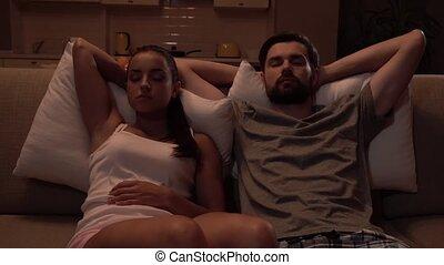 Girl and guy sit on sofa and sleep. They breath very deep....