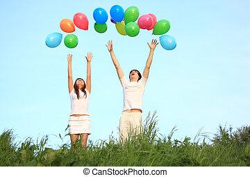girl and guy start multicoloured balloons in sky