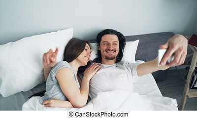 Girl and guy taking selfie in bed with smartphone camera...
