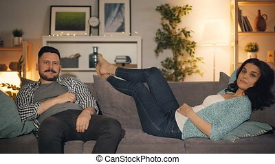Girl and guy watching TV in apartment on couch enjoying mass...