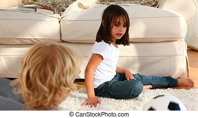 Girl and her brother playing a game on the carpet