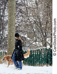 a girl and dog/snowing