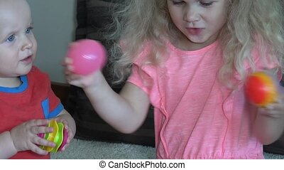 girl and her little brother boy playing with colorful balls at home.