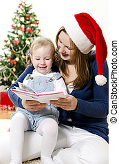 Girl and her mom reading book at Christmas