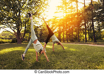 Girl and her mother doing a handstand in the park