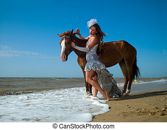 Girl and horse at the beach - A girl in a white dress beside...
