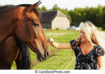 Girl and horse - Cute blond girl touching nose of a horse