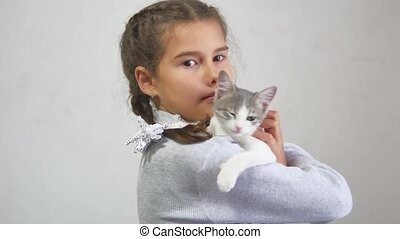 girl and kitten. kitten is playing bites teen girl holding a kitten on her hands indoor. girl teen and cat
