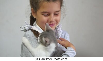 girl and kitten. teen girl holding a kitten on her hands indoor. girl teen and cat