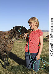 Girl and Lamb - a cute blonde girl interacts with her lamb...