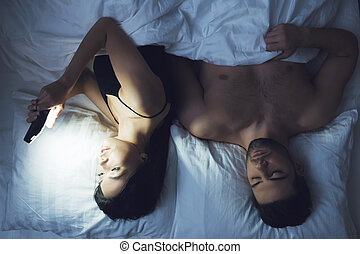 Girl and man are lying on bed in underwear and look at...