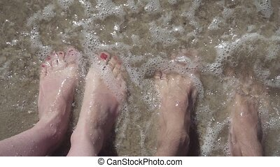 girl and man legs in the ocean. slow motion video