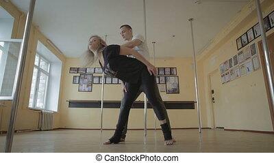 Girl and men dancing strip plastic in dance studio stock...