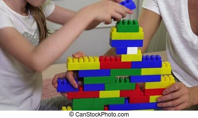 Girl and mother build tower of play bricks