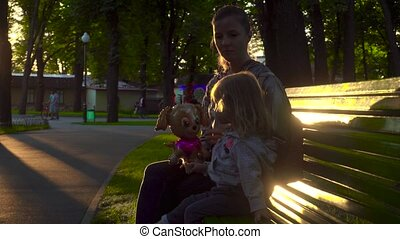 Girl and mother sitting on bench in the park in evening
