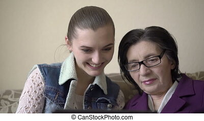 Girl and old woman using a tablet at the sofa, smiling, caring