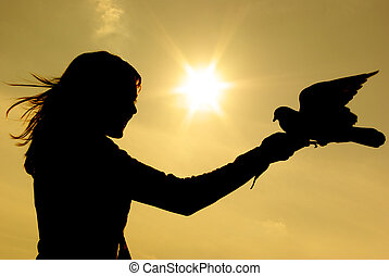 Girl and pigeon at the sunset