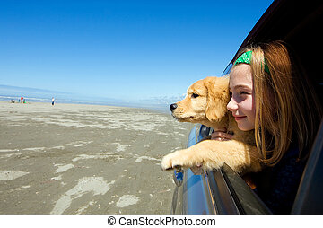 girl and puppy in car window