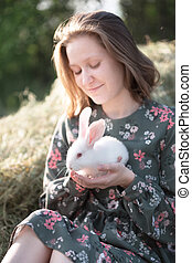 girl and rabbit  in the garden. happy childhood in the ...