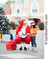 Girl And Santa Claus With Wish Letter - Full length of girl...