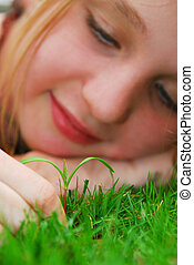 Girl and seedling - Closeup on a face of a young girl...