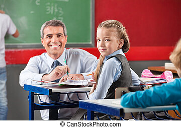 Girl And Teacher Sitting At Desk In Classroom