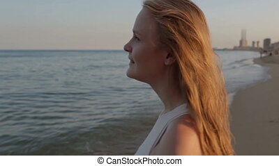 Girl and the sea. - Girl looking to the sea at sunset. Shot...