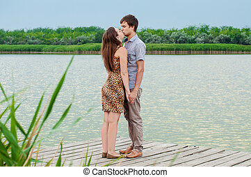 girl and the young man on the dock by the river