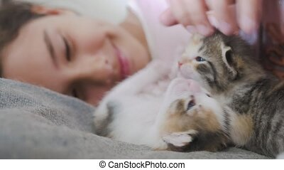 girl and two cute kittens concept - happy little girl with cat in bed at home. schoolgirl baby and cat love of pets the kitten. girl and lifestyle kittens concept