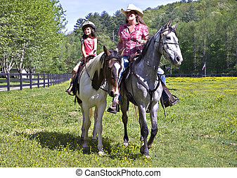Girl and Woman Riding Horses - A woman and a young girl on...