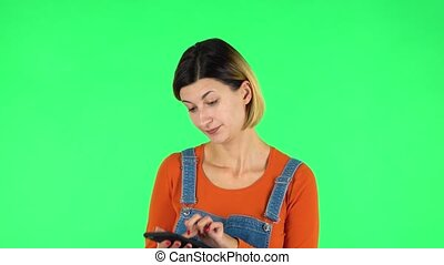 Girl angrily texting on her phone. Brown-eyed girl with an earring in her ear dressed an orange sweater and denim overalls on a green screen in the studio