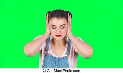 Girl angry covering her ears with her hands on green screen at studio, slow motion. Girl with two hair-buns, wearing denim overalls and pink t-shirt.