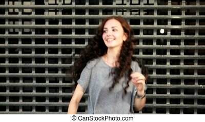 Girl applausing in funny way in front of metal fence