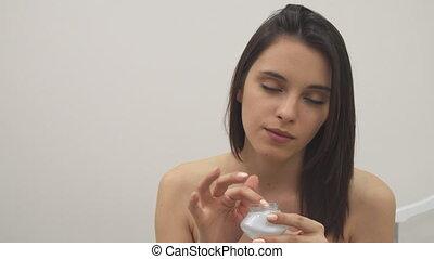 Girl applies facial treatment